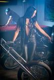 kvinna som poserar nära mopeder, man som spelar biljard Arkivbild