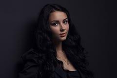 kvinna som poserar på en svart bakgrund Arkivfoto