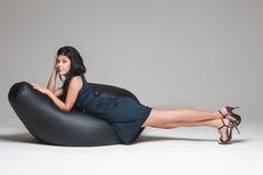 Kvinna som poserar på sittkudden Arkivbild