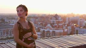 Kvinna som poserar på taket på solnedgången stock video