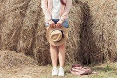 Kvinna som poserar runt om händer av en höstack arkivbild