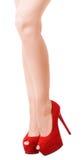 Kvinna som poserar vid sexiga ben i röda mockaskinnskor Arkivbild