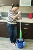 Kvinna som pressar golvmopp Arkivbild