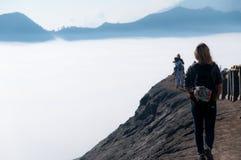 Kvinna som promenerar överkanten av vulkan bredvid dimma och Arkivfoton