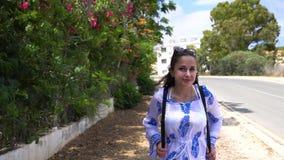 Kvinna som promenerar vägen i vändkretsar Härlig kvinnahandelsresande som promenerar vägen stock video