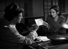 Kvinna som räcker över ett kuvert till en kriminalare arkivfoto