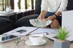 Kvinna som räknar dollar på tabellen - affärsidé, minnestavla och fi royaltyfria bilder