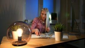 Kvinna som räknar kassa på det funktionsdugliga skrivbordet Attraktiv blond kvinnlig i rutigt skjortasammanträde på natten i rum  arkivfilmer
