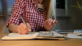 Kvinna som räknar kassa på det funktionsdugliga skrivbordet Attraktiv blond kvinnlig i rutigt skjortasammanträde på natten i rum  lager videofilmer