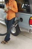 Kvinna som räknar pengar på bensinpumpen Arkivbild