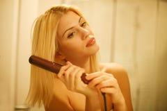 Kvinna som rätar ut hår med rätat ut royaltyfri bild