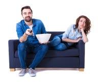 Kvinna som är borrad hållande ögonen på tv med pojkvännen som isoleras på vit Royaltyfri Fotografi