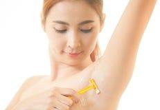 Kvinna som rakar armhålan med den isolerade rakkniven Fotografering för Bildbyråer