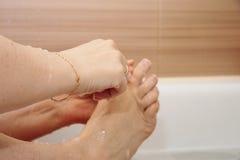 Kvinna som rakar henne ben som sitter i badrummet arkivbild