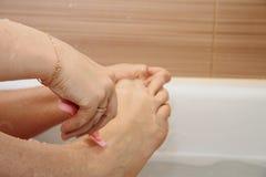 Kvinna som rakar henne ben som sitter i badrummet fotografering för bildbyråer