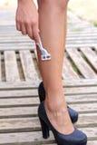 Kvinna som rakar hennes ben med en manuell rakkniv royaltyfria bilder