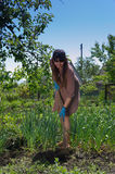 Kvinna som rensar grönsakträdgården Royaltyfri Foto