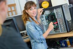 Kvinna som reparerar datoren som vänder för att tala till kunden arkivbilder