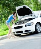 Kvinna som reparerar den brutna bilen royaltyfri foto