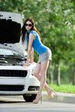 Kvinna som reparerar den brutna bilen på gatan Royaltyfri Bild