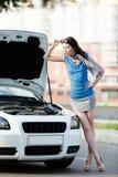 Kvinna som reparerar den brutna bilen på huvudvägen Royaltyfria Foton
