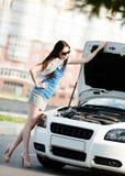 Kvinna som reparerar den brutna bilen på vägen Fotografering för Bildbyråer