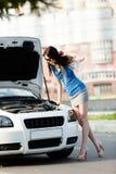 Kvinna som reparerar den brutna cabrioleten på gatan royaltyfria bilder