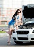 Kvinna som reparerar den brutna cabrioleten på huvudvägen royaltyfri fotografi