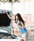 Kvinna som reparerar den brutna cabrioleten på vägen royaltyfri bild