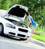 Kvinna som reparerar den brutna vitbilen royaltyfri fotografi