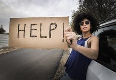 Kvinna som reser det ensamma innehavhjälptecknet Arkivbild