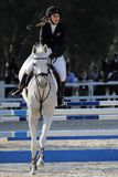 Kvinna som rider den vita hästen under banhoppningkonkurrens Arkivbilder
