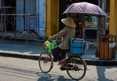 Kvinna som rider en cykel med paraplyet i gatorna av Hoi An, Viet arkivfoto