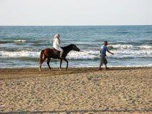 Kvinna som rider en häst med hijab vid stranden Den muslimska kvinnan som sitter på hästrygg, en hästman, riktar bredvid Kaspiska royaltyfri foto