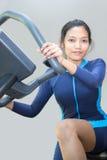 Kvinna som rider en motionscykel royaltyfri fotografi