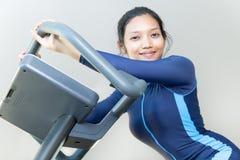 Kvinna som rider en motionscykel arkivbilder