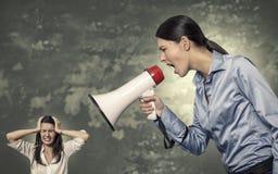 Kvinna som ropar genom att använda megafonen till den stressade kvinnan Arkivbild