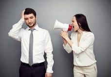 Kvinna som ropar i megafon på den trötta mannen Royaltyfri Bild