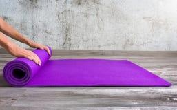 Kvinna som rullar hennes matta purpurfärgade yoga Royaltyfria Bilder