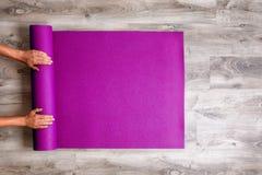 Kvinna som rullar hennes matta yoga Royaltyfria Foton