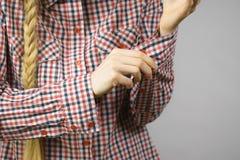 Kvinna som rullar upp muffarna i kontrollerad skjorta Arkivfoton