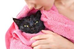 Kvinna som rymmer den gulliga svarta blöta katten efter ett bad royaltyfria foton