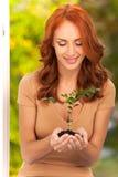 Kvinna som rymmer den lilla växten i henne händer Royaltyfri Bild