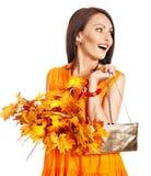 Kvinna som rymmer den orange leafen och handväskan. Arkivbild
