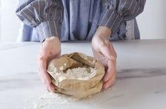 Kvinna som rymmer den pappers- påsen med vitt mjöl K?ksbord och kock bredvid det, vem som g?r f?rberedelser f?r att baka arkivbild