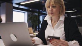 Kvinna som rymmer den plast- kreditkorten för online-shopping och använda arkivfilmer