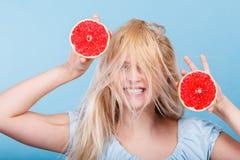 Kvinna som rymmer den röda grapefrukten som har galet windblown hår arkivbild
