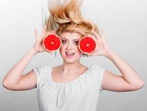 Kvinna som rymmer den röda grapefrukten som har galet windblown hår arkivfoto