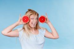 Kvinna som rymmer den r?da grapefrukten som har galet windblown h?r royaltyfria bilder