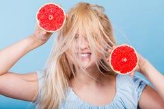 Kvinna som rymmer den r?da grapefrukten som har galet windblown h?r royaltyfri foto